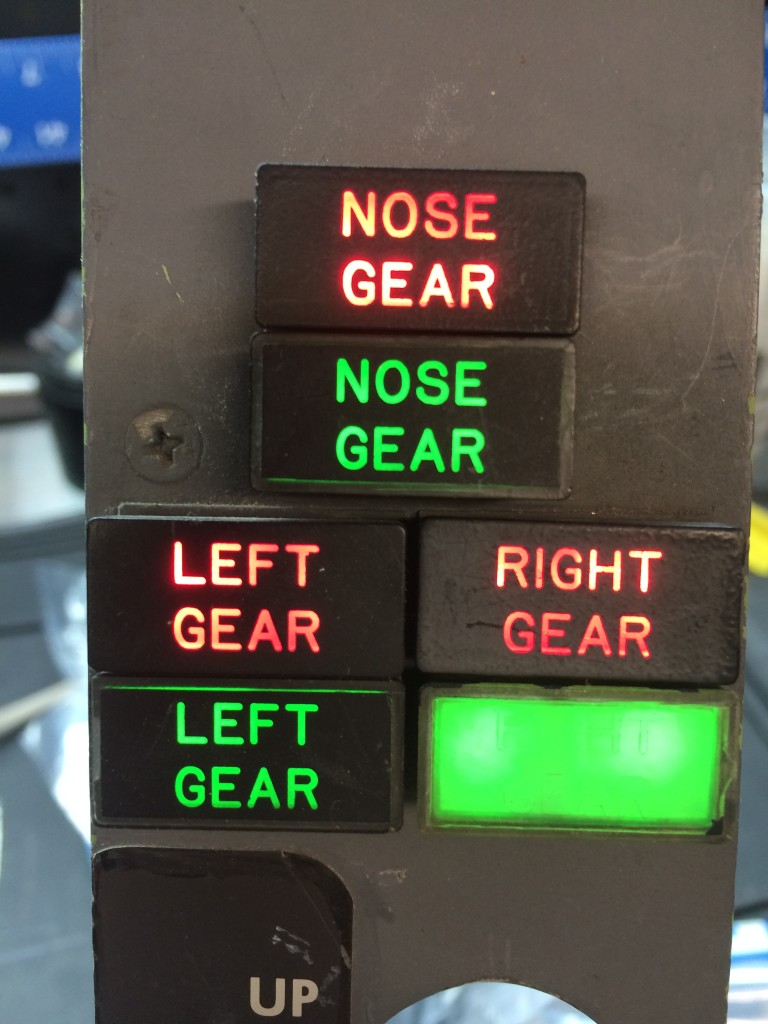 "Red lights indicate gear in transit or abnormal condition, green lights indicate gear down and locked. After replacing four burned out GE 387 lamps, the ""test all"" lights up all six annunciators. The right gear down indicator at bottom right needs to be re-surfaced, but the others are in pretty good shape."